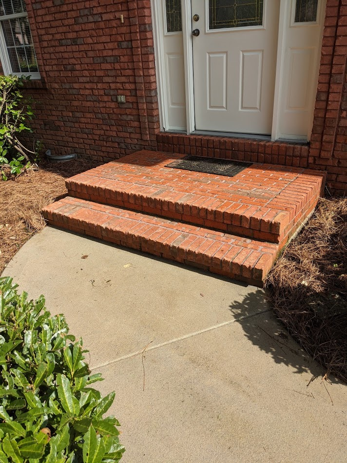 Red brick steps have been power washed to remove algae